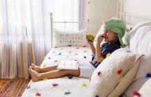Petit garçon assis sur le canapé avec une pomme et une tablette numérique en riant — Photo de stock