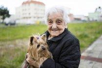 Portrait d'une femme senior avec Yorkshire Terrier sur ses bras — Photo de stock