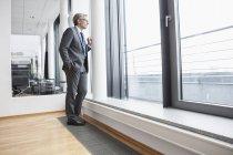 Administrador exitoso mirando a través de la ventana en la oficina - foto de stock