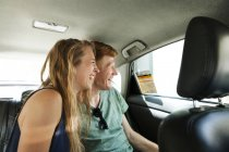 Laughing couple sitting in taxi looking through window — Stock Photo