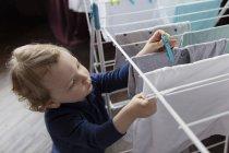 Маленький хлопчик, надягаючи одяг кілочок сушіння Пральня — стокове фото