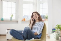 Woman at home sitting in chair talking on cell phone — Stock Photo