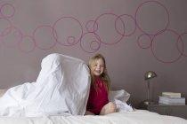 Дівчинка сидить на ліжку батьків ховається під простирадлом посміхається — стокове фото