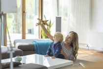Mother and son playing with toy plane in living room — Stock Photo