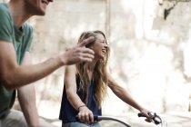Смеется женщина с велосипеды рядом с ее партнером — стоковое фото