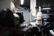 Junge Elektroniker in Werkstatt reparieren und Blick in die Kamera — Stockfoto