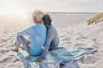 Vista posteriore di coppie che si siedono sulla spiaggia che guarda il mare — Foto stock