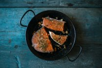 Salmon fillets in pan with parsley and garlic — Stock Photo