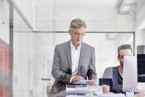 Empresário maduro no escritório usando tablet digital — Fotografia de Stock