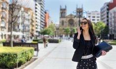 Красивая молодая женщина со смартфоном прогуливается по городу — стоковое фото