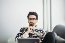 Портрет задумчивого человека, смотрящего на цифровой планшет — стоковое фото