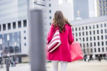 Young woman with shopping bags walking in the city, rear view — Stock Photo