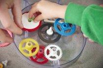 Mani che montano ruote dentate in plastica — Foto stock