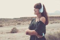 Mujer joven escuchando música, sonriendo felizmente - foto de stock
