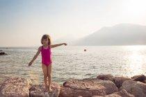 Italia, Brenzone, Ragazza in piedi sulla riva rocciosa del lago — Foto stock