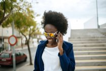 Portrait of young woman wearing mirrored sunglasses talking on mobile phone — Stock Photo
