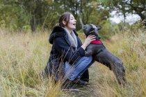Женщина сидит с собакой на траве в природе — стоковое фото