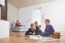 Father lying on floor with children painting with mother on background — Stock Photo