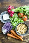 Top view of chickpeas with tomatoes, carrots, red cabbage, red radishes, lettuce and feta cheese — Stock Photo
