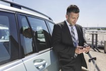 Businessman leaning against car — Stock Photo