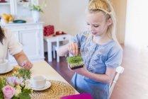 Mädchen am Esstisch mit Kresse — Stockfoto