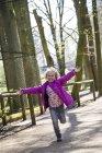 Felice bambina che corre con le braccia tese — Foto stock