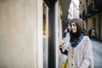 Spain, Barcelona, smiling young woman in the city looking at shop window — Stock Photo