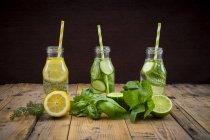 Три скляні пляшки води таблиці, приправлений різних фруктів та трав — стокове фото