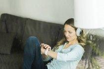 Женщина дома на диване в наушниках смотрит на смартфоны — стоковое фото