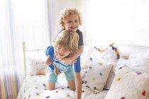 Dois irmãozinhos jogando no sofá em casa — Fotografia de Stock