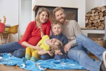 Portrait of happy family sitting on blanket on floor at home — Stock Photo