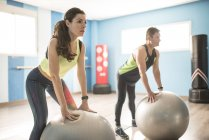 Mature couple training with fitness ball in gym — Stockfoto