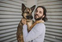 Portrait de souriant jeune homme tenant chien — Photo de stock