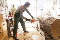 Резчик по дереву в мастерской работает над деревом для скульптуры с бензопилой — стоковое фото