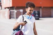 Lächelnde junge Frau mit Kopfhörern und Handy im Freien — Stockfoto