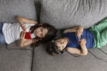 Siblings lying on the couch listening  music with their headphones and smartphones — Stock Photo