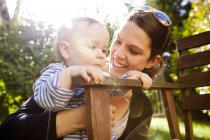 Happy mother with her little son in the garden — Stock Photo