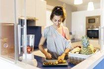 Jeune femme dans la cuisine à préparer des fruits — Photo de stock