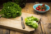 Visão de closeup de aluguer alface em cortar placa com faca e tomates — Fotografia de Stock