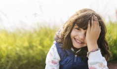 Портрет улыбающейся маленькой девочки, закрывающей глаза рукой — стоковое фото