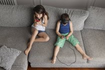 Siblings sitting on the couch listening  music with their headphones and smartphones — Stock Photo
