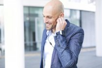 Smiling businessman with earbuds and smartwatch — Stock Photo