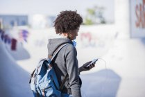 Young woman with backpack and cell phone outdoors — Stock Photo