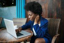 Giovane donna che lavora con il computer portatile in un caffè di strada — Foto stock
