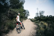 Mountain biker having a rest on a trail — Stock Photo