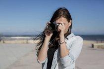 Молодая женщина с фотоаппаратом на берегу моря — стоковое фото