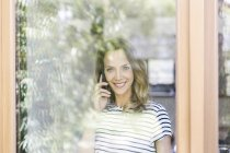 Портрет усміхається жінка на мобільний телефон за шибці — стокове фото