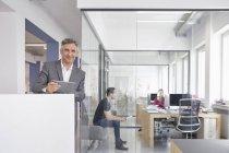 Empresario maduro en oficina moderna con tableta digital - foto de stock