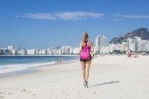 Vista posteriore della donna che fa jogging sulla spiaggia — Foto stock