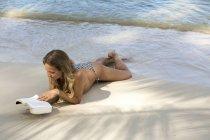 Таиланд, женщина читает книгу на пляже — стоковое фото